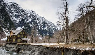 In this April 2014 photo provided by Olympic National Park,  a log cabin teeters on the eroding bank of the Quinault River in Olympic National Park in Washington.  The cabin has been added to the state list of most endangered historical properties.  Built in 1930, the chalet was used as a lodge, summer ranger station and emergency shelter. It's located in the southwest corner of the park, 13 miles up the Graves Creek trail in the Enchanted Valley.  (AP Photo/Olympic National Park)