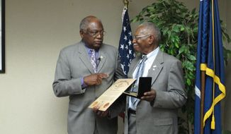 U.S. Rep. Jim Clyburn, D-S.C., left, presents a Congressional Gold Medal to William Ramseur, right on Wednesday, May 14, 2014, in Columbia, S.C. Ramseur, of Columbia, was a member of the Montford Point Marines who integrated the Marine Corps in the 1940s. (AP Photo)