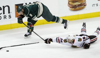 Minnesota Wild center Mikko Koivu (9), of Finland, and Chicago Blackhawks center Marcus Kruger (16), of Sweden, chase the puck during the first period of Game 6 of an NHL hockey second-round playoff series in St. Paul, Minn., Tuesday, May 13, 2014. (AP Photo/Ann Heisenfelt)