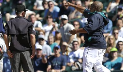 Seattle Mariners manager Lloyd McClendon, right, throws his cap after he was ejected by first base umpire Lance Barksdale, left, Wednesday, May 14, 2014, after McClendon argued the call that Mariners' John Buck had struck out swinging in the eighth inning of a baseball game against the Tampa Bay Rays, in Seattle. (AP Photo)