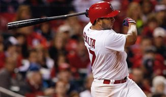 St. Louis Cardinals' Jhonny Peralta follows through on an RBI single during the sixth inning of a baseball game against the Chicago Cubs on Tuesday, May 13, 2014, in St. Louis. (AP Photo/Scott Kane)