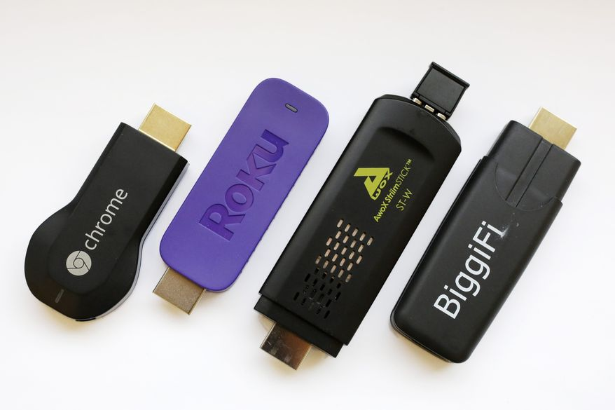 This April 24, 2014 photo shows four streaming stick devices, from lef: Google Chromecast, Roku Streaming Stick, AwoX StriimStick, and BiggiFi, in New York. (AP Photo/Mark Lennihan)
