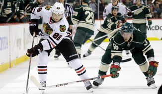 Chicago Blackhawks right wing Patrick Kane (88) and Minnesota Wild left wing Erik Haula (56), of Finland, chase the puck during the second period of Game 6 of an NHL hockey second-round playoff series in St. Paul, Minn., Tuesday, May 13, 2014. (AP Photo/Ann Heisenfelt)