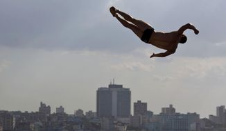 10ThingstoSeeSports - An athlete dives from the Red Bull Cliff Diving World Series platform in the final round, in Havana, Cuba, Saturday, May 10, 2014. The world's best cliff divers jumped from the 27-meter platform positioned on the historic Morro Castle in Havana. (AP Photo/Ramon Espinosa, File)