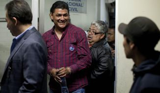 Handcuffed radio host Marlon Puente Rimula, second from left, smiles as he is escorted by police to a courtroom, in Guatemala City, late Tuesday night, May 13, 2014. Guatemalan police arrested the radio host who leads a fan organization for the Club Municipal soccer team for allegedly inciting fellow fans to kill a supporter of a rival team. Puente Rimola and two other men were arrested for the April 27 beating and stabbing death of Kevin Diaz, a 17-year-old fan of the rival team, Comunicaciones. (AP Photo/Moises Castillo)