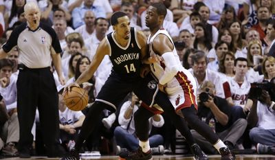 Miami Heat guard Dwyane Wade (3) applies pressure on Brooklyn Nets guard Shaun Livingston (14) during the first half of Game 5 of a second-round NBA playoff basketball game in Miami, Wednesday, May 14, 2014. (AP Photo)