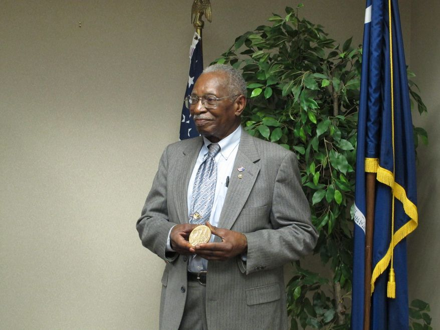 William Ramseur holds up his Congressional Gold Medal presented to him by U.S. Rep. Jim Clyburn on Wednesday, May 14, 2014, in Columbia, S.C. Ramseur, of Columbia, was a member of the Montford Point Marines who integrated the Marine Corps in the 1940s. (AP Photo)