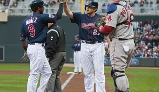 Minnesota Twins Eduardo Nunez (9), left, celebrates with Chris Parmelee (27), center after Nunez hit a two run home run against  Boston Red Sox starting pitcher Jake Peavy (44) as catcher A.J. Pierzynski (40) looks on during the second inning of a baseball game in Minneapolis, Tuesday, May, 13, 2014.(AP Photo/Craig Lassig)