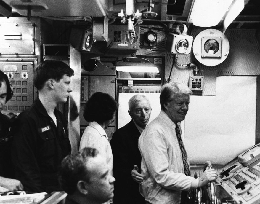 U.S. President Jimmy Carter maneuvers the nuclear submarine U.S.S. Los Angeles at the wheel off the coast of Port Canaveral, Florida, Friday, May 27, 1977, while Admiral Hyman Rickover (behind Carter) looks on. (AP Photo)