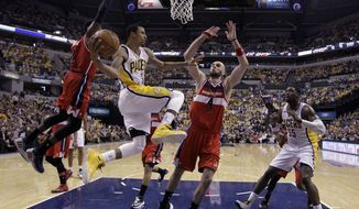 Indiana Pacers' George Hill (3) makes a pass against Washington Wizards' Marcin Gortat (4) and John Wall (2) during the second half of game 5 of the Eastern Conference semifinal NBA basketball playoff series Tuesday, May 13, 2014, in Indianapolis. Washington defeated Indiana 102-79. (AP Photo/Darron Cummings)