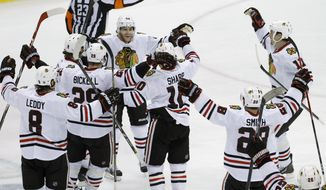 Teamamtes swarm Chicago Blackhawks right wing Patrick Kane, center, to celebrate his game-winning goal off Minnesota Wild goalie Ilya Bryzgalov to beat the Wild 2-1 during overtime of Game 6 of an NHL hockey second-round playoff series in St. Paul, Minn., Tuesday, May 13, 2014. (AP Photo/Ann Heisenfelt)