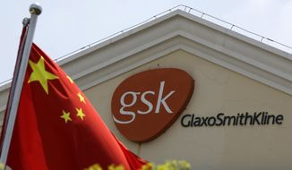 FILE - In this July 24, 2013 file photo, a Chinese flag is hoisted in front of a GlaxoSmithKline building in Shanghai, China. Police accused a British executive of drug maker GlaxoSmithKline on Wednesday, May 14, 2014, of leading a sprawling scheme to bribe doctors and hospitals to use its products. (AP Photo/Eugene Hoshiko, File)