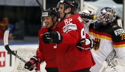 Switzerland forward Simon Moser, left and forward Damien Brunner celebrate a goal during the Group B preliminary round match between Germany and Switzerland at the Ice Hockey World Championship in Minsk, Belarus, Wednesday, May 14, 2014. (AP Photo/Darko Bandic)