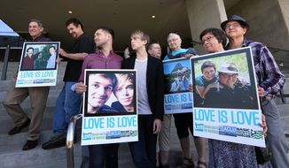 Supporters of same-sex marriage hold photos of themselves and their family members or partners on the steps of the Wayne L Morse U.S. Courthouse Wednesday, May 14, 2014, in Eugene, Ore. A federal judge will hear arguments Wednesday about whether a national group can defend Oregon's ban on same-sex marriage because the state's attorney general has refused to do so. (AP Photo/The Register-Guard, Chris Pietsch)