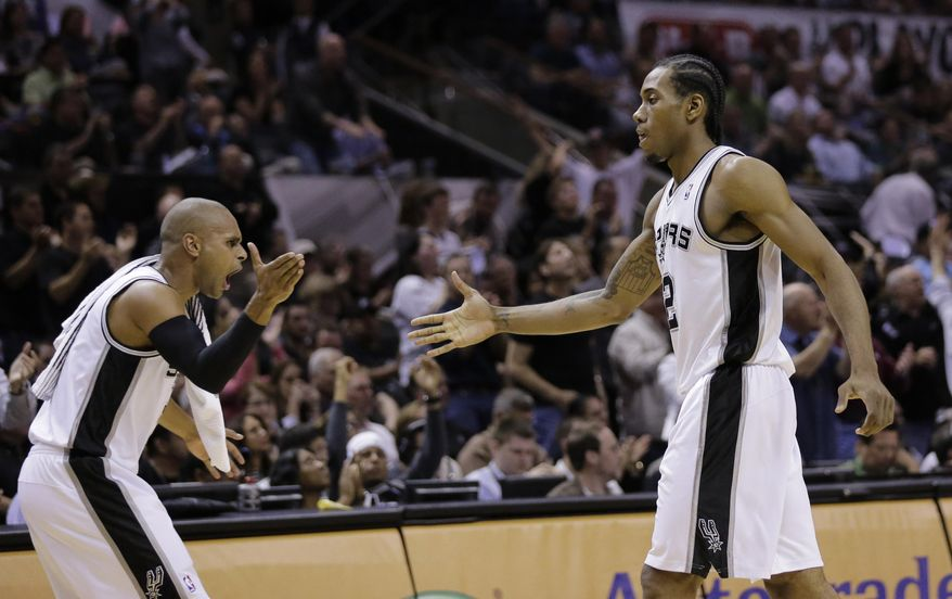 San Antonio Spurs' Patty Mills, left, slaps hands with Kawhi Leonard as Leonard walks off the court during the first half of Game 5 of a Western Conference semifinal NBA basketball playoff series against the Portland Trail Blazers, Wednesday, May 14, 2014, in San Antonio. (AP Photo/Eric Gay)