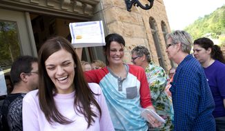 ** FILE ** In this May 10, 2014, file photo, Kristin Seaton, center, of Jacksonville, Ark., holds up her marriage license as she leaves the Carroll County Courthouse in Eureka Springs, Ark., with her partner, Jennifer Rambo, left, of Fort Smith, Ark., in Eureka Springs, Ark. The Arkansas Supreme Court has rejected the state attorney general's request for a stay of a judge's ruling that overturned Arkansas' constitutional ban on gay marriage, Wednesday, May 14, 2014. (AP Photo/Sarah Bentham, file)