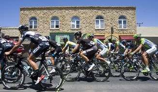Race leader Bradley Wiggins, center rear in yellow jersey, pedals through Arroyo Grande, Calif., with other competitors during Stage 5 of the Tour of California cycling race Thursday, May 15, 2014. (AP Photo/The Tribune, David Middlecamp)  MAGS OUT  NO SALES