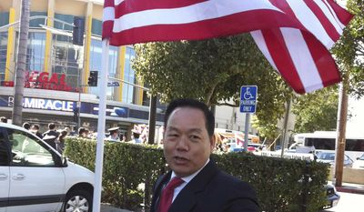 FILE - In this Feb. 16, 2012 file photo released by Anna Wu, American businessman Vincent Wu poses with an American flag as he waits to welcome China's then-Vice President Xi Jinping on his visit to Los Angeles, Calif. A Chinese court sentenced Vincent Wu on Thursday, May 15, 2014 to 20 years in prison on charges of heading a mob that kidnapped rivals and operated illegal casinos, and rejected his claim that he was tortured by police. (AP Photo/Courtesy of Anna Wu, File)