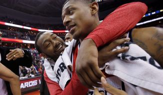 John Wall embraces fellow guard Bradley Beal after the Wizards beat the Celtics on April 2 to clinch the franchise's first playoff berth in six years. The pair celebrated an overtime victory in Game 2 of their first-round series against the Bulls (below). Washington clinched the series in five games. (associated press photographs)
