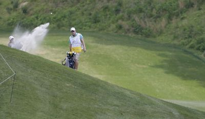Austin Ernst blasts out of a fairway sand trap on the eighth hole during the first round of the Kingsmill Championship golf tournament at the Kingsmill resort in Williamsburg, Va., Thursday, May 15, 2014.   Ernst parred the hole and finished the round at 6-under-65. (AP Photo/Steve Helber)