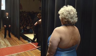 In this April 25, 2014 photo, Justin Stees, 18, waits for his prom date and grandmother Julie Stees, 59, as they meet for the grand march at Prophetstown High School in Prophetstown, Ill. (AP Photo/Sauk Valley Media, Alex T. Paschal)