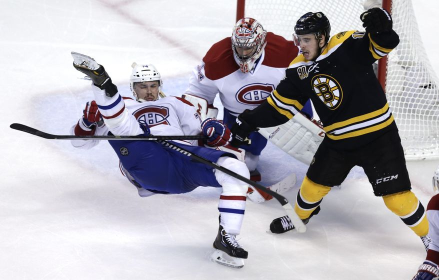 Montreal Canadiens defenseman Alexei Emelin, left, is upended by Boston Bruins right wing Reilly Smith, right, in front of goalie Carey Price during the third period in Game 7 of a second-round NHL hockey Stanley Cup playoff series in Boston, Wednesday, May 14, 2014. (AP Photo)