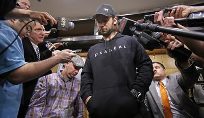 Pittsburgh Penguins' Kris Letang is surrounded by media as he takes a break from cleaning out his locker at the Consol Energy Center in Pittsburgh, Thursday, May 15, 2014. (AP Photo/Gene J. Puskar)