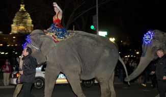 FILE - This March 19, 2013 file photo shows a performer waving as elephants with the Ringling Bros. and Barnum & Bailey show walk in front of the Capitol in Washington on their way to the Verizon Center. The parent company of the Ringling Bros. and Barnum & Bailey Circus says it has received a nearly $16 million settlement from the Humane Society of the United States and other animal-rights groups that filed a frivolous lawsuit against them. The lawsuits in federal court in Washington have dragged on for more than a decade. In 2012, a judge said the case, alleging abusive treatment of elephants, was frivolous and forced the circus' owner, Vienna, Virginia-based Feld Entertainment, to spend millions in legal fees.  (AP Photo/Alex Brandon, File)