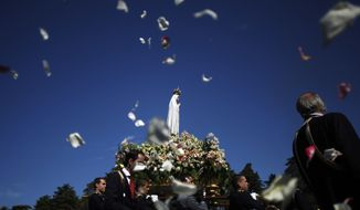 AP10ThingsToSee - Worshippers throw flower petals to the statue of the Our Lady of Fatima, in Fatima, Portugal, Tuesday, May 13, 2014. Every year on May 12 and 13 thousands of Catholic pilgrims arrive to Fatima Sanctuary to attend Masses and pray in honor of the Virgin Mary, where it is believed she was witnessed by three shepherd children in 1917. (AP Photo/Francisco Seco)
