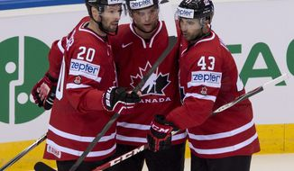 Team Canada's Cody Hodgson, center, is congratulated by teammates Troy Brouwer, left, and Nazem Kadri, after he scored the first goal against Denmark during first period action at the IIHF World Hockey Championship in Minsk, Belarus, Thursday, May 15, 2014. (AP Photo/The Canadian Press, Jacques Boissinot)