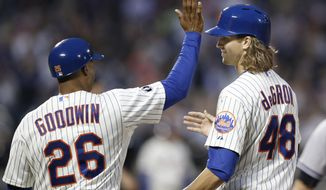 New York Mets first base coach Tom Goodwin (26) congratulates Mets starting pitcher Jacob deGrom after deGrom hit a third-inning single in a baseball game against the New York Yankees in New York, Thursday, May 15, 2014. (AP Photo/Kathy Willens)