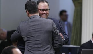 Assemblyman John Perez, D-Los Angeles, receives congratulations from Assemblyman Mike Gatto, D-Los Angeles, after his measure to place a rainy day fund on the November ballot was approved by the Assembly in  Sacramento, Calif., Thursday, May 15, 2014.  Lawmakers in both houses approved the bill Perez negotiated before stepping down as speaker this week  It places a proposed constitutional amendment before the voters that will create a budget reserve funded primarily from excess capital gains revenue during boom years as well as an annual contribution equal to 1.5 precent of the state's general fund. (AP Photo/Rich Pedroncelli)