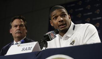 FILE - In this May 13, 2014 file photo, St. Louis Rams seventh-round draft pick Michael Sam, right, speaks during a news conference as head coach Jeff Fisher listens at the NFL football team's practice facility in St. Louis. The head of an advocacy group for gay and lesbian athletes helped the Rams prepare for the arrival of Sam. (AP Photo/Jeff Roberson, File)