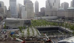 The pavilion entrance to the National September 11 Memorial Museum, left, is next to one of the memorial reflecting pools, right, at the World Trade Center, Thursday, May 15, 2014 in New York. President Barack Obama is to attend the dedication of the underground museum Thursday before it opens to the public May 21. (AP Photo/Mark Lennihan)
