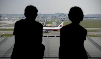 FILE - In this April 10, 2014 file photo, a couple are silhouetted as they watch a Malaysia Airlines plane on the tarmac from the viewing gallery at Kuala Lumpur International Airport in Sepang, Malaysia. Malaysia Airlines said its net loss expanded 59 percent in the first quarter, hit by loss of revenue from China after the disappearance of Flight 370 two months ago. The flag carrier said Thursday, May 15, 2014, its net loss surged to 443.4 million ringgit ($137.8 million), up from 278.8 million ringgit in the January-to-March period last year. Revenue however, still rose 1.7 percent to 3.6 billion ringgit ($1.1 billion).  (AP Photo/Joshua Paul, File)
