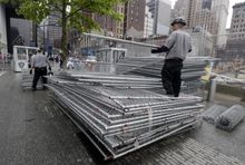 Workers on the plaza of the National September 11 Memorial & Museum stack sections of fencing removed from the venue's perimeter, in New York, Thursday, May 15, 2014.  The plaza is scheduled to open to the public Thursday evening. (AP Photo/Richard Drew)