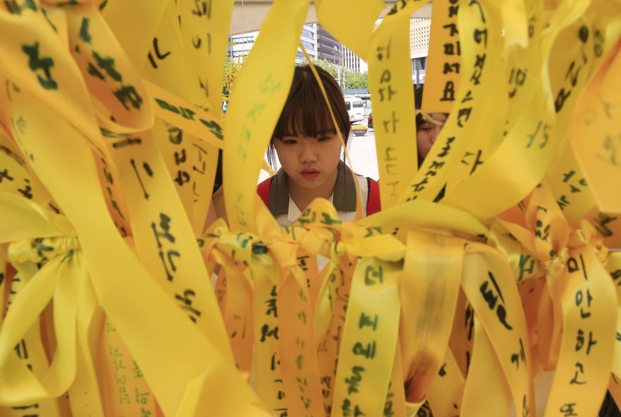 A high school student reads massages written on ribbons for the victims of the sunken ferry Sewol at a group memorial altar in Seoul, South Korea, Thursday, May 15, 2014. Prosecutors indicted the captain of the sunken South Korean ferry and three crew members on homicide charges Thursday, alleging they were negligent and failed to protect more than 300 people missing or dead in the disaster. Less serious indictments were issued against the 11 other crew members responsible for navigating the vessel.(AP Photo/Ahn Young-joon)