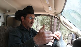 Otero cattle rancher association president Gary Stone drives his truck in Weed, New Mexico, Thursday, May 15, 2014. The Otero County Cattleman's Association is pitted against the National Forest Service over a fence intended to protect wildlife that the agency installed around a small creek where the ranchers' cattle drink water. (AP Photo/Juan Carlos Llorca)