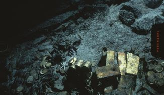 FILE - This 1989 file photo shows gold bars and coins from the S.S. Central America, a mail steamship, which sunk in a hurricane in 1857, about 160 miles off the North Carolina coast. Columbus-America Discovery Group, owned by fugitive treasure hunter Tommy Thompson, argues in a Thursday, May 16, 2014 filing that it has the exclusive rights to the treasure from the shipwreck. (AP Photo/File)