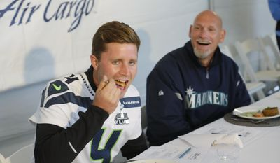 Celebrity cook-off judges Steven Hauschka, left, kicker for the Seattle Seahawks NFL football team, and Jay Buhner, right, former right fielder for the Seattle Mariners baseball team, sample dishes made with Copper River King Salmon, Friday, May 16, 2014, as they judge a cook-off competition following the delivery of the first Copper River salmon shipment of the year from Cordova, Alaska to the Alaska Airlines Cargo facility in Seatac, Wash. (AP Photo/Ted S. Warren)
