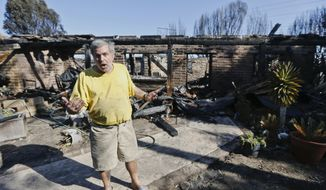 Greg Saska stands outside his home that was destroyed by wildfire as he talks about his loss, Thursday, May 15, 2014, in Carlsbad, Calif. Nine fires in all were burning an area of more than 14 square miles (36 square kilometers) amid a heat wave and dry conditions, said San Diego County officials, who warned also of poor air quality with black and gray smoke wafting over the region. The wildfires drove tens of thousands from their homes and shut down schools and amusement parks, including Legoland.  (AP Photo/Lenny Ignelzi)