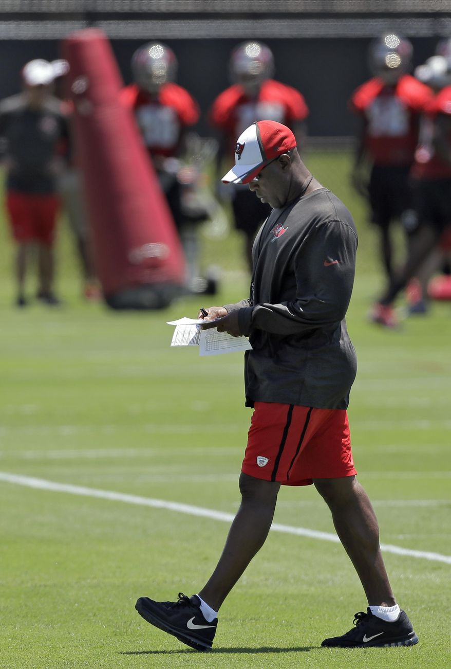 Tampa Bay Buccaneers head coach Lovie Smith checks his notes during NFL football rookie camp Friday, May 16, 2014, in Tampa, Fla. (AP Photo/Chris O'Meara)