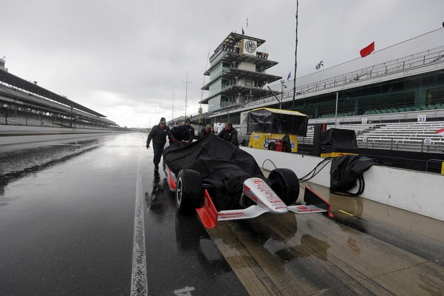 The crew of Tony Kanaan, of Brazil, pushes the car back to the garage area as rain halted practice for Indianapolis 500 IndyCar auto race at the Indianapolis Motor Speedway in Indianapolis, Friday, May 16, 2014. (AP Photo/Darron Cummings)