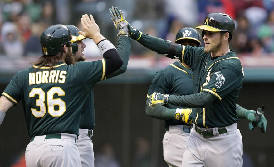 Oakland Athletics' Josh Reddick, right, celebrates with teammates after hitting a grand slam off Cleveland Indians starting pitcher Zach McAllister in the second inning of a baseball game, Friday, May 16, 2014, in Cleveland. Yoenis Cespedes, Jed Lowrie, and Derek Norris scored. (AP Photo/Tony Dejak)