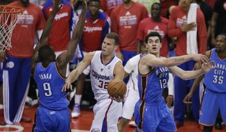 Los Angeles Clippers' Blake Griffin, center, drives to the basket as he is defended by Oklahoma City Thunder's Serge Ibaka, left, of Congo, and Steven Adams during the first half in Game 6 of the NBA Western Conference semi-finals on Thursday, May 15, 2014, in Los Angeles. (AP Photo/Jae C. Hong)