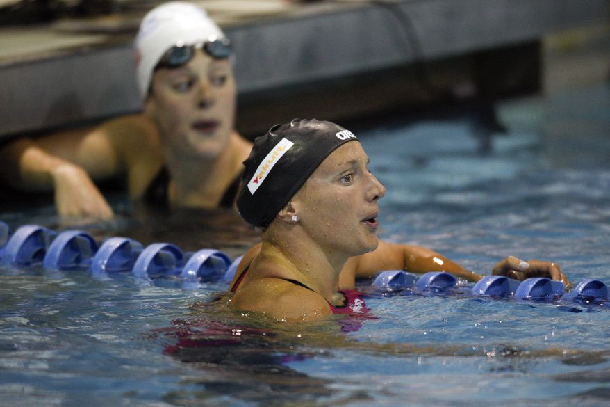 Katina Hosszu, of Hungary, right, catches her breath after beating Allison Schmitt, background, to win the 200-meter freestyle at the Grand Prix swim meet in Charlotte, N.C., Friday, May 16, 2014. (AP Photo/Nell Redmond)