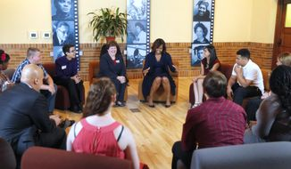 First lady Michelle Obama leads the discussion during a roundtable with high school students at Monroe School in Topeka, Kan., Friday, May 16, 2014. (AP Photo/Orlin Wagner)