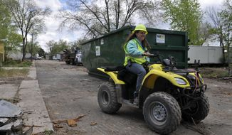 Kristin Chilcutt rides by as she monitors the progress of the demolition in Bella Vista Mobile Home Park on May 14, 2014 in Evans, Colo.  Health officials in February warned that trash, old food, and household cleaning products left behind in the flood debris would cause problems once the weather warmed. But before the cleanup could start, the park owners had to figure out how to pay for the work and how they could legally remove the damaged trailers that were owned by their tenants. (AP Photo/The Greeley Tribune, Joshua Polson)