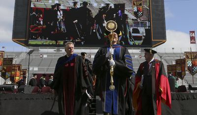 Virginia Governor Terry McAuliffe, left, walks in the academic processional to conclude the Virginia Tech Class of 2014 graduation ceremony held in Lane Stadium on the Virginia Tech campus in Blacksburg Friday May 16 2014.  (AP Photo/The Roanoke Times, Matt Gentry)