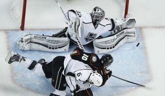 Los Angeles Kings goalie Jonathan Quick blocks a shot from Anaheim Ducks right wing Corey Perry with the help of Jake Muzzin during the second period in Game 7 of an NHL hockey second-round Stanley Cup playoff series in Anaheim, Calif., Friday, May 16, 2014. (AP Photo/Chris Carlson)